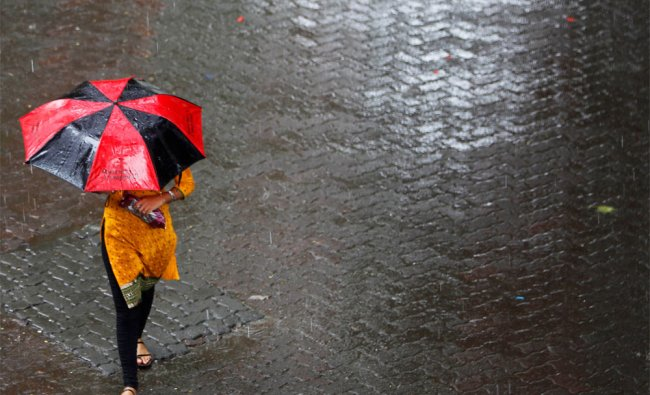 A woman holds an umbrella during a monsoon shower in Mumbai