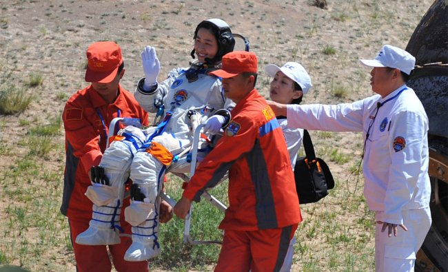 China\'s first female astronaut Liu Yang waves as she is carried after coming out of re-entry capsule