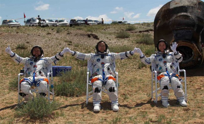 Chinese astronauts wave after coming out of the re-entry capsule