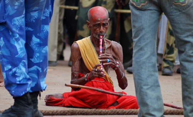 An Indian holy man plays the flute during the closing ceremony of the nine-day long Rath Yatra...