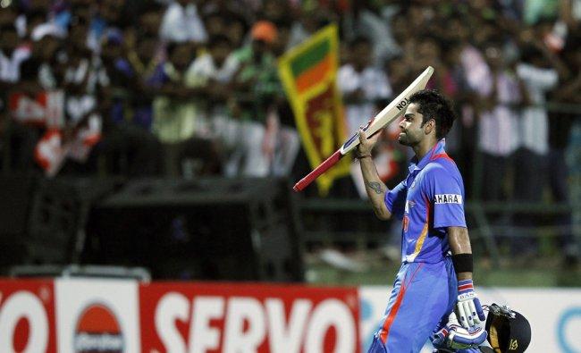 Virat Kohli raises his bat for spectators as he walks off the field after his dismissal...