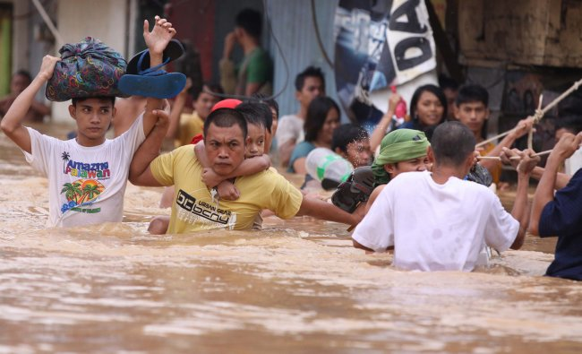 Residents hang on to a rope as they pass strong currents along a flooded area in Marikina, east...