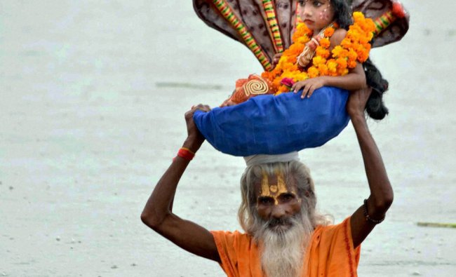 A man along with a kid enact crossing of Yamuna by Vasudev and Krishna...