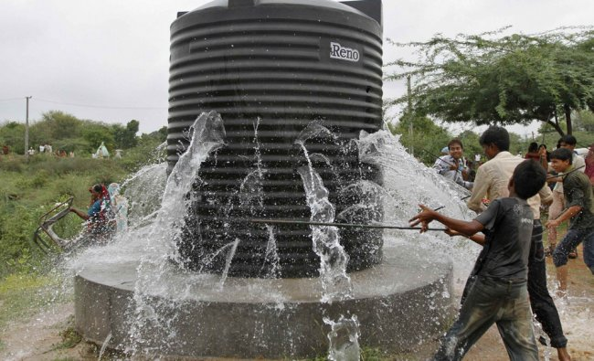 Villagers damage a water tank on land allotted by the state government to build a university...