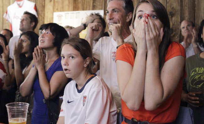 People react as they watch a television broadcast of the United States women\'s soccer team taking...
