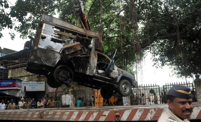 A crane lifts a burnt television broadcast van from the Azad maidan ground in Mumbai