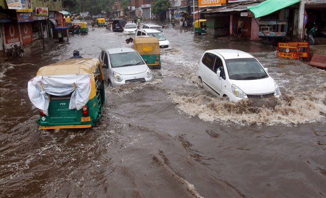 People and traffic move on a flooded raod after rains in Ahmedabad on Sunday...