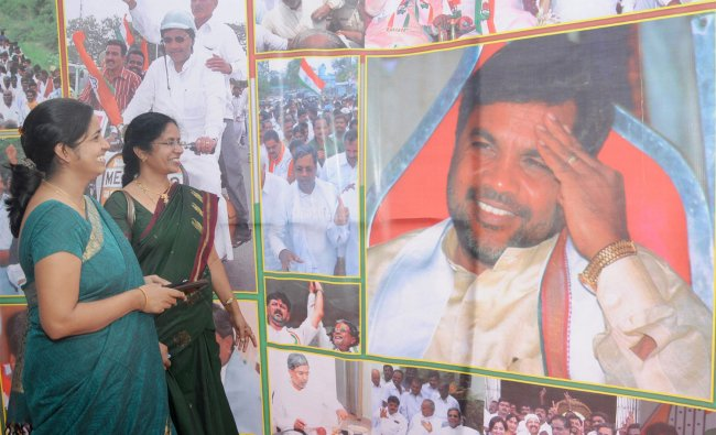 People watching the photographs of Opposition Leader Siddaramaiah on his 65th birthday celebration..