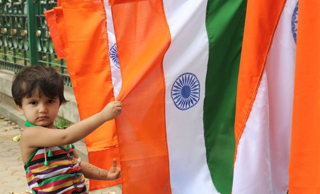 A child watching the Indian national flags as a street vendor arranged at Cubbon Park in Bangalore..