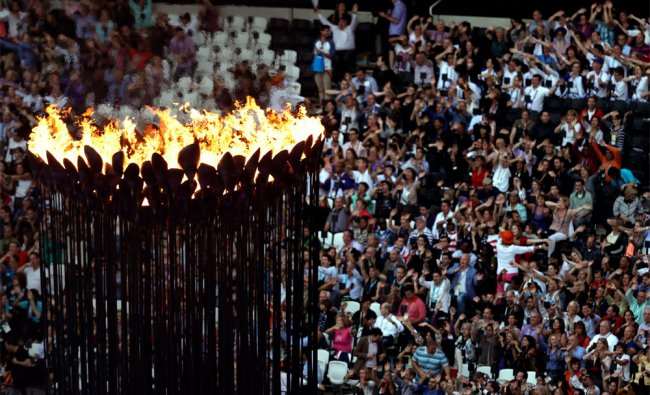 The Olympic flame burns as spectators gather in Olympic Stadium to attend the Closing Ceremony