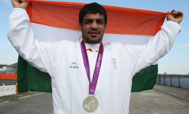 Sushil Kumar poses with his Silver medal and National flag after the bout