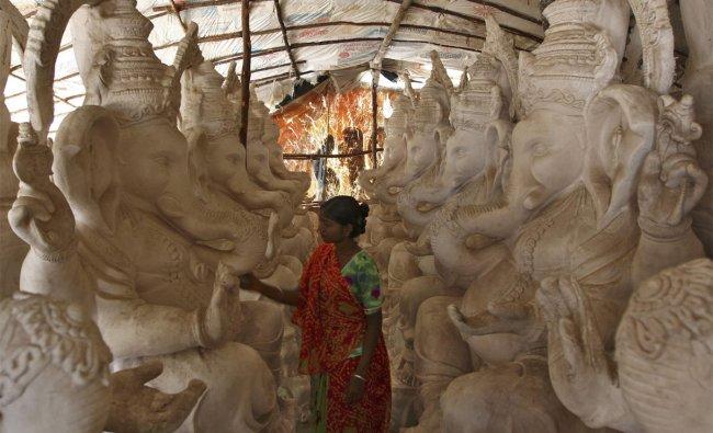 An artisan works on an idol of Hindu elephant god Ganesh, the deity of prosperity, at a workshop