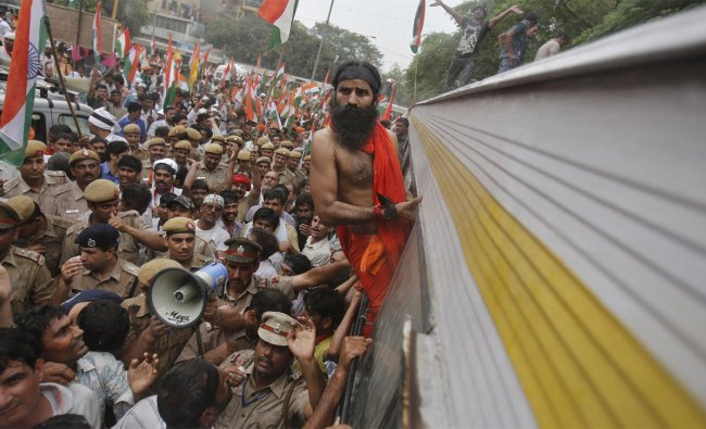 Baba Ramdev (C) leans out of a bus window after he was detained by police