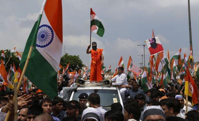 Baba Ramdev rides on top of a vehicle as he leaves Ramlila Maidan