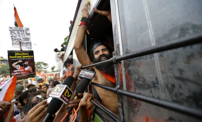 Baba Ramdev reacts to the media by the window of a bus