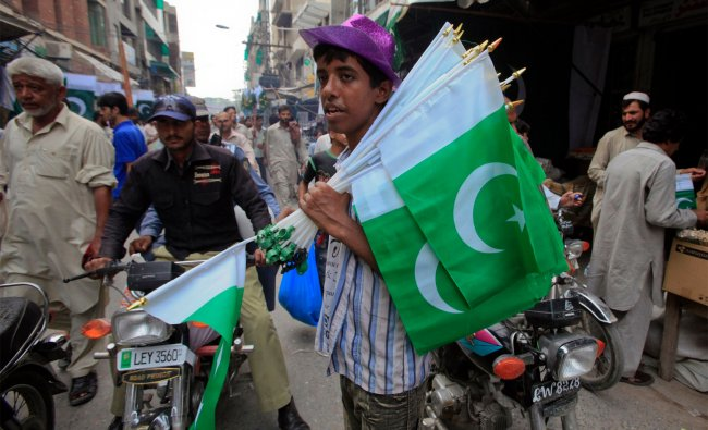 A boy sells Pakistan\'s national flags at a market ahead of Pakistan\'s independence day...