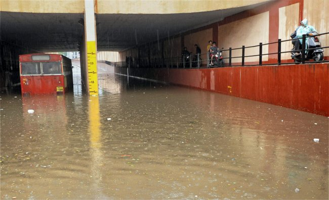 A bus wades through a flooded underpass after heavy downpour in Ahmedabad ...