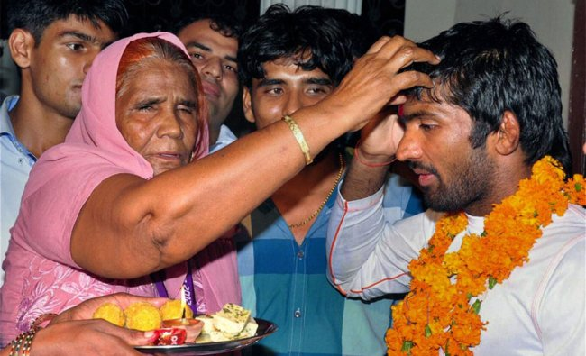 Wrestler Yogeshwar Dutt, who won a bronze medal at the London Olympics, being welcomed by his mother