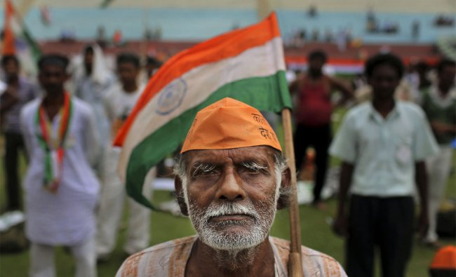 An elderly man holds the Indian flag as he listens to patriotic songs