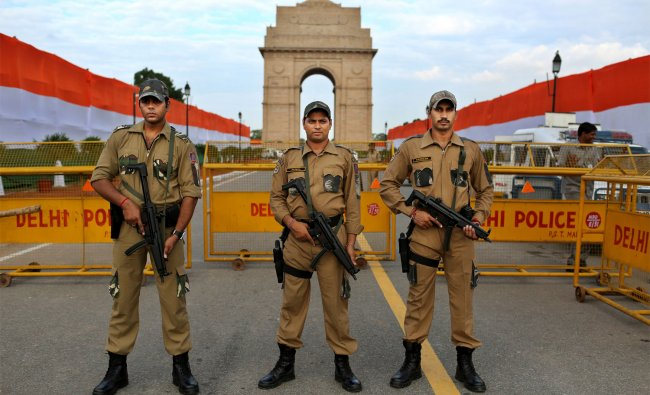 Police SWAT team members stand guard in front of the India Gate Monument ...