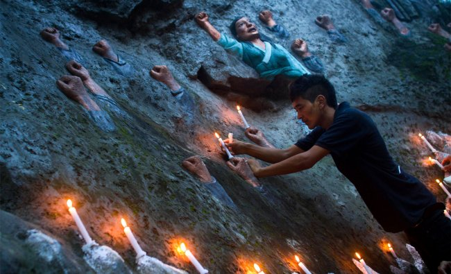 An exile Tibetan places candles on Tibetan martyr\'s wall in solidarity with self immolated Tibetans.