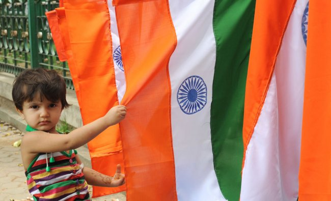 A small girl watching the Indian national flag