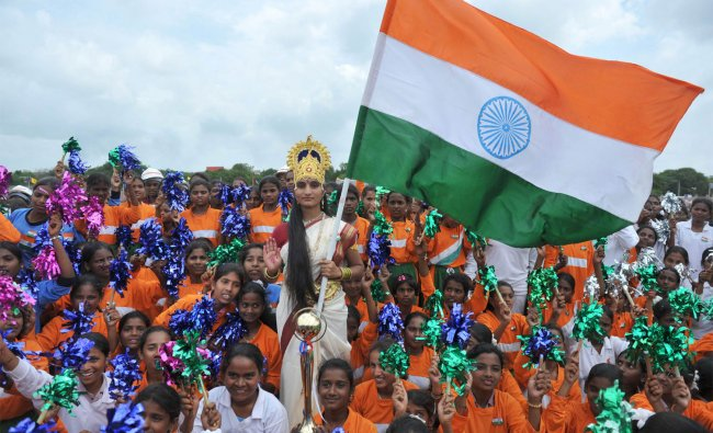 woman dressed as Bharath Matha (Mother of India) poses with a tricolour flag