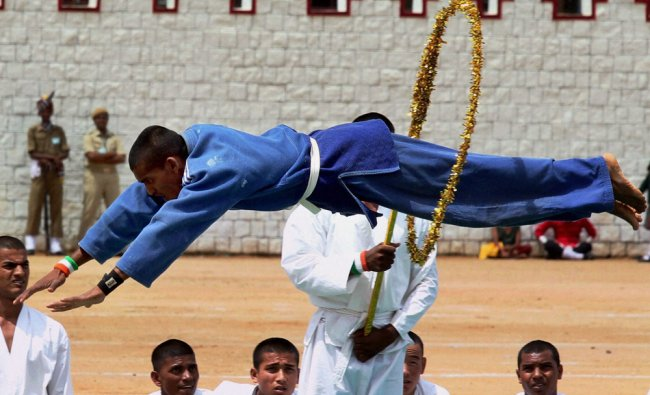 A Judo performer jumps through a wheel during 66th Independence day...
