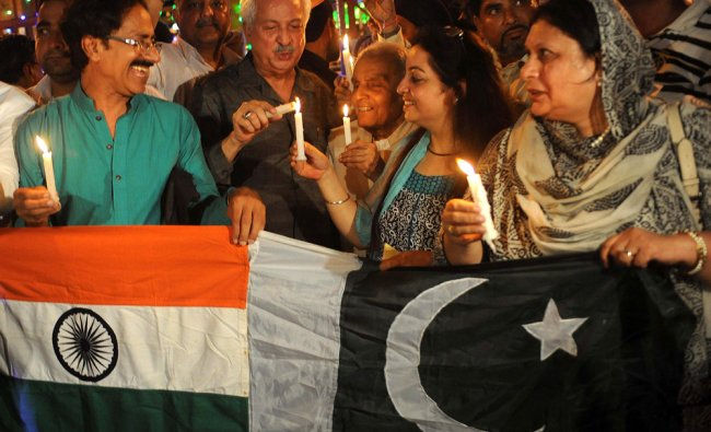 Pakistani and Indian revellers hold up candles and Indo-Pak joint national flags ...