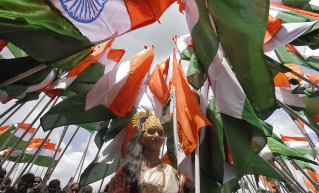 A woman dressed as Mother India poses with India\'s national flags...