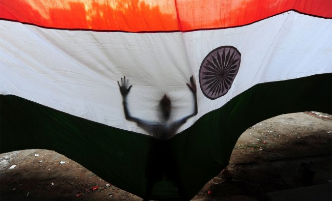A boy tries to control a national flag from the wind as it is installed at a wholesale market ...
