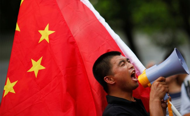 A protester yells slogans during a march in front of the Japanese consulate in Shanghai