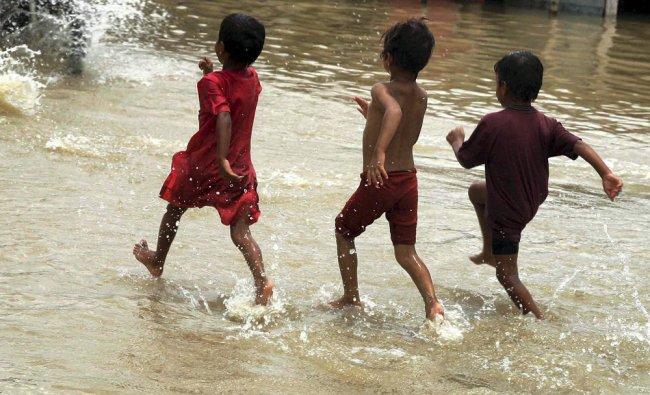 Children run through a flooded road inundated by swollen Ganga and Yamuna ...