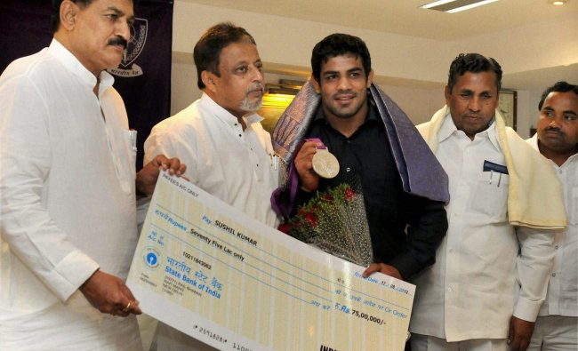 Union Minister for Railways Mukul Roy presenting a cheque for rupees 75 lakhs to Sushil Kumar...