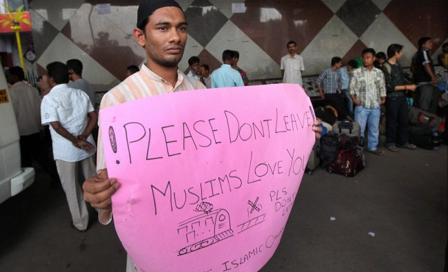 A member of Students Islamic Forum holds a placard requesting migrants of Northeastern states...