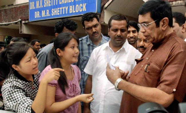 Students of North Eastern states showing threat messages on the mobile phone to Congress MP Oscar...