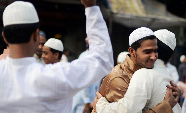 Muslims embrace after offering Eid al-Fitr prayers near the Jama Masjid Mosque