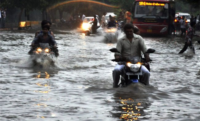 Vehicles move through a water logged street during heavy rains in Bhopal...