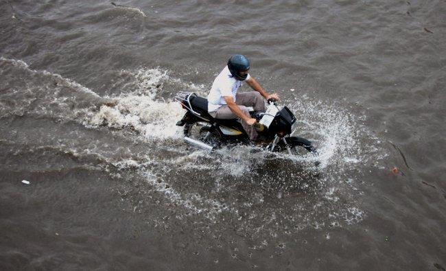 A motorcyclist wade through a waterlogged street ...