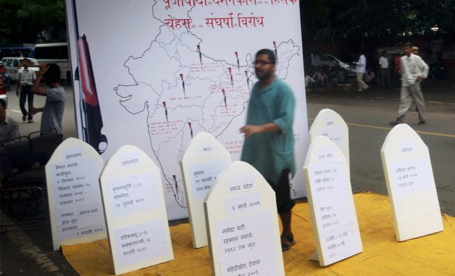 An activist of Jan Morcha standing near mock grave stones of victims of land acquisition