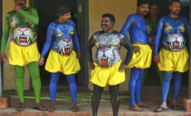 Dancers in body paint wait to take part in a performance during festivities...