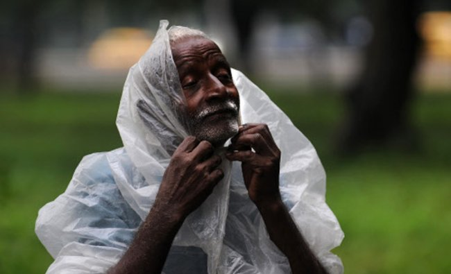 An Indian tea-vendor covers himself with a plastic sheet for protection from rain in Kolkata ...