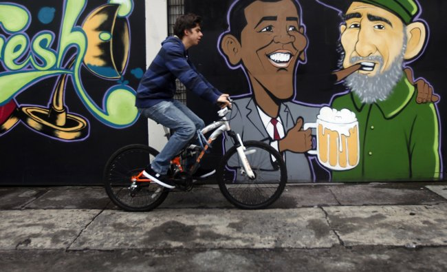 A man cycles past a wall graffiti of caricatures of U.S. President Barack Obama (L) and Cuban...