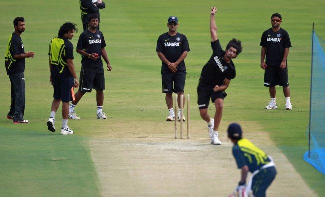 Mahendra Singh Dhoni, center, watches teammate Ishant Sharma bowl to Gautam Gambhir