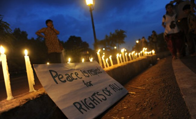 A placard is pictured next to candles during a vigil organised by Delhi Solidarity ...