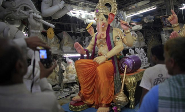 A devotee takes pictures of an idol of Hindu elephant god Ganesh, the deity of prosperity...
