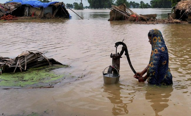 A woman collects drinking water from a hand-pump in flood-hit Daniyawan village...
