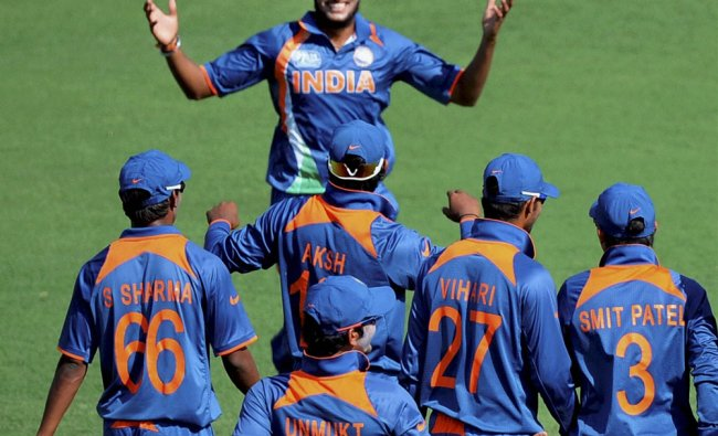 Ravi Kant Singh of India celebrates with team mates after taking the wicket...