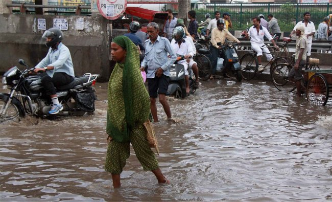 Vehicles wade through a waterlogged road after heavy rains in Gurgaon ....