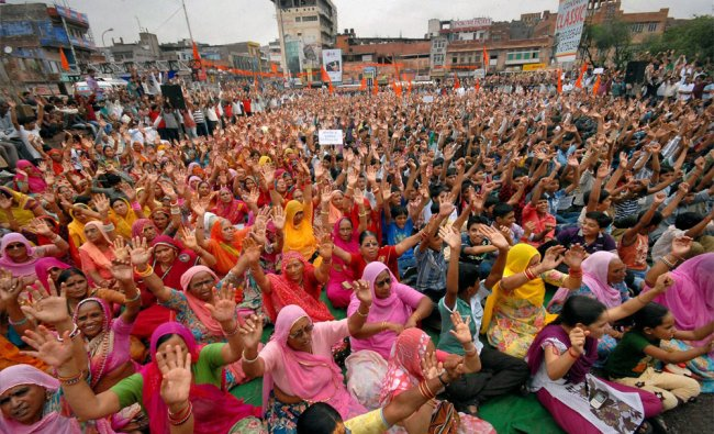 People shout slogans at a protest over violence in Assam, in Jodhpur...
